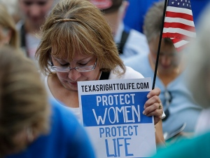 Supports of an abortion bill pray during an anti-abortion rally at the Texas Capitol, Monday, July 8, 2013, in Austin, Texas. The fight over access to abortion in Texas resumed Monday with thousands expected to attend a marathon Senate hearing and a nighttime anti-abortion rally at the Capitol. (AP Photo/Eric Gay)